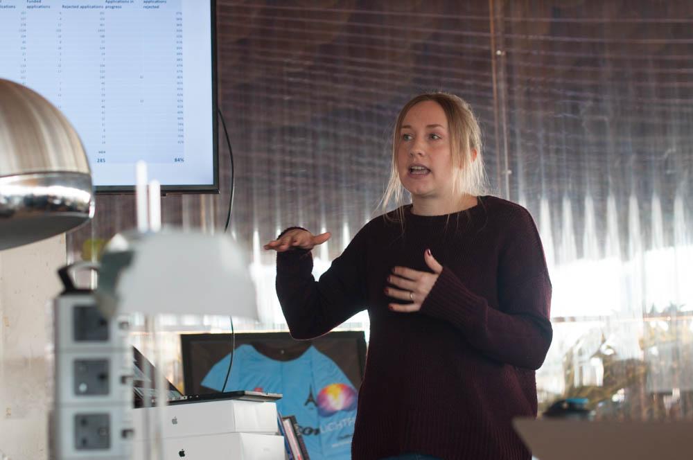 Jacqui Lowe explaining data on a PowerPoint slide
